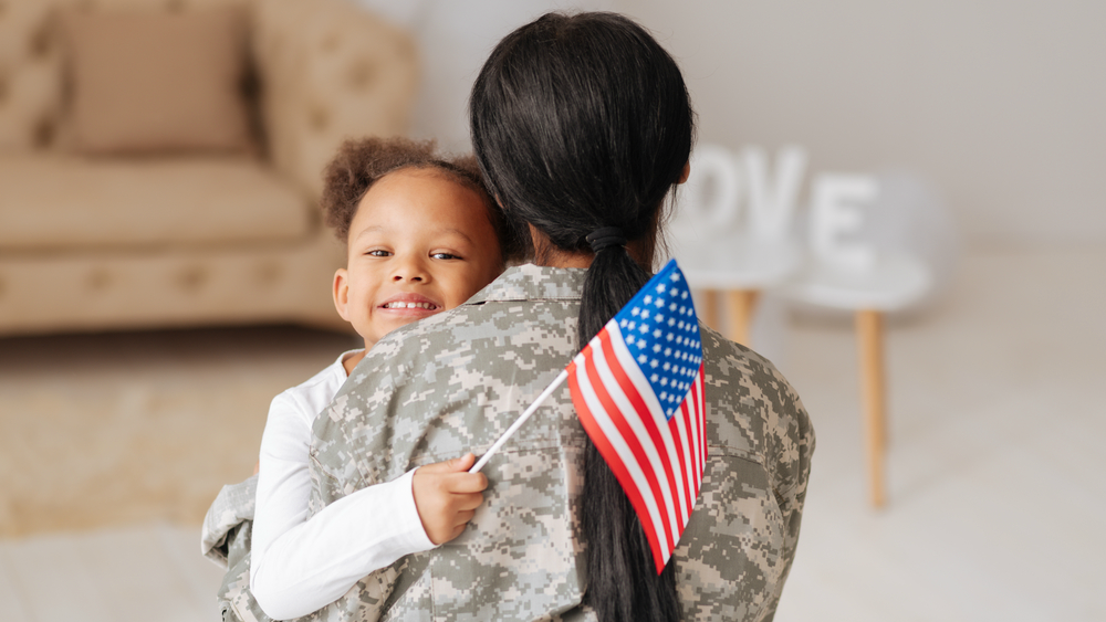 Female service member hugging daughter holding American flag after returning from duty