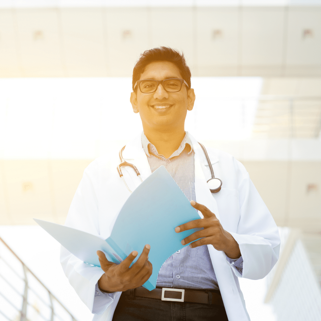 Doctor looking through file stopping to smile at the camera