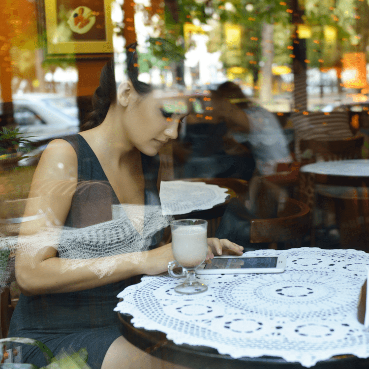 Woman using tablet in restaurant to find information on locums assignment