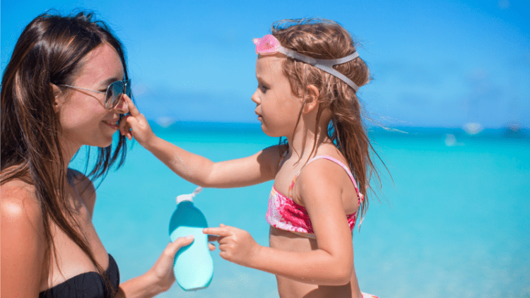 Child putting sunscreen on laughing mother's nose on day at the beach in North Carolina while on locums assignment